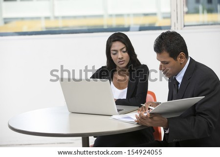 Indian business man and woman working on a laptop while having a meeting. - stock photo