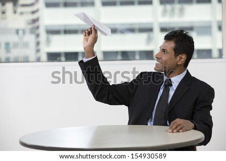 Indian business man holding a paper airplane. Business Concept. - stock photo
