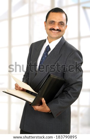 Indian business man holding file on his hand .