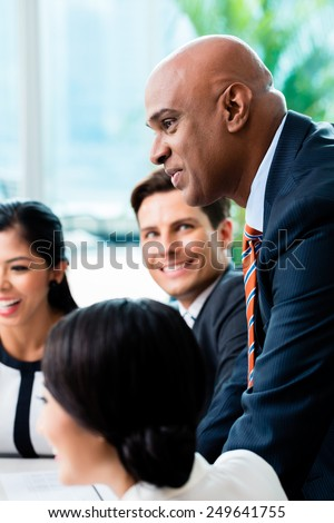 Indian Business man leading team meeting of diversity people in office - stock photo