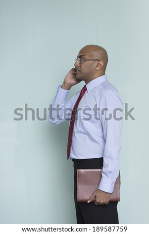 Indian Business man Outside Office using his Mobile Phone. - stock photo