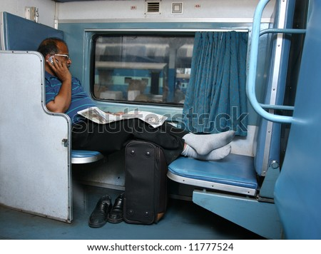 Indian Business man using cellphone on the train. - stock photo