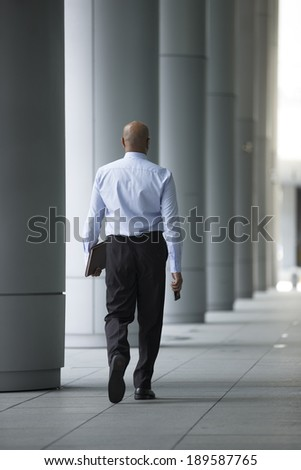 Indian Business man walking down the street with his back to camera - stock photo