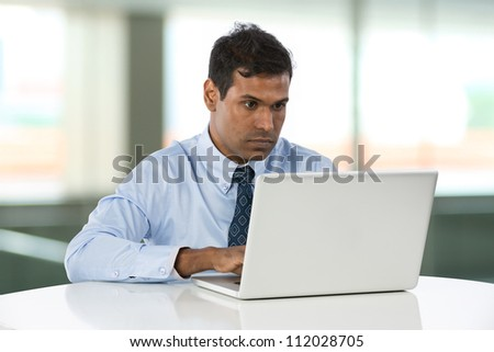 Indian Business man working on his laptop. - stock photo