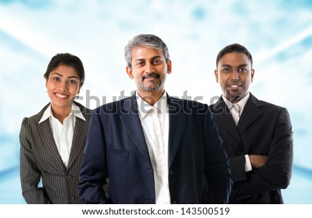 Indian business team.  Asian Indian businessmen and businesswoman in group. Teamwork concept standing inside office building. Good looking Indian model. - stock photo