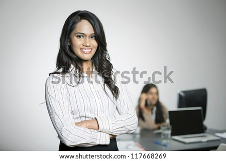 Indian Business woman with her colleague in the background working.