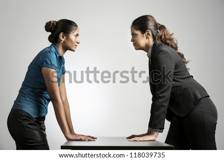 Indian business women staring at each other.  Two business rivals having a standoff.