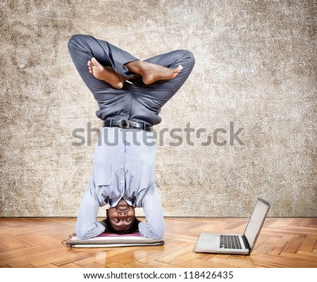 Indian businessman doing yoga headstand pose and looking at his laptop in the office at brown textured background - stock photo
