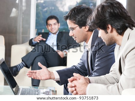 indian businessman explaining on laptop in meeting