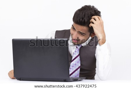 Indian Businessman frustrated with work sitting in front of a laptop.