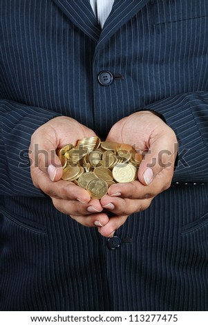Indian Businessman Holding Gold Coins - stock photo