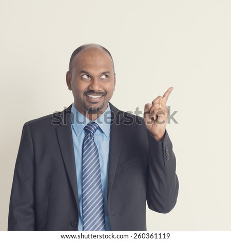 Indian businessman looking and pointing to blank copy space in vintage tone, plain background - stock photo