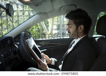 Indian businessman sitting in his parked car and using Tablet PC. - stock photo