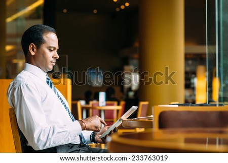 Indian businessman sitting in the cafe and reading news on the digital tablet - stock photo