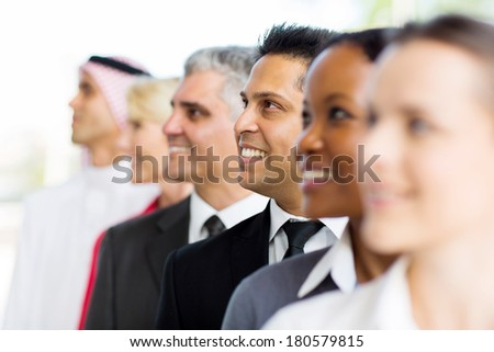 indian businessman standing in a row with co-workers - stock photo
