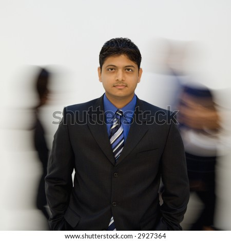 Indian businessman standing with hands in pockets while others walk by. - stock photo