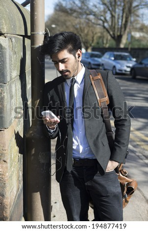 Indian businessman using smartphone in urban street. Wearing jacket and tie. Britain, UK.