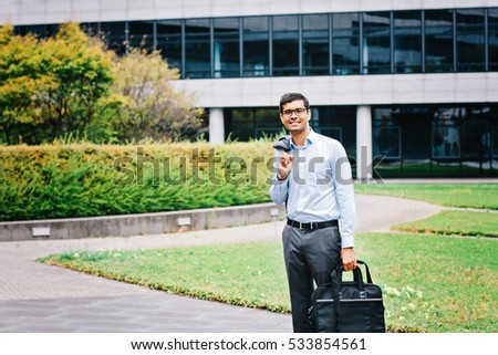 Indian businessman with bag standing outdoor
