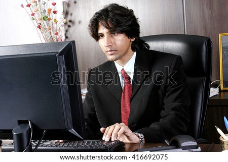 Indian businessman working with computer at his office - stock photo