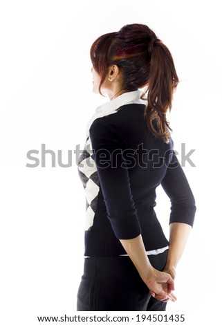 Indian businesswoman looking up with hands behind back - stock photo
