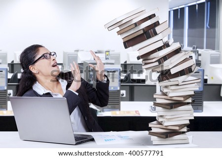 Indian businesswoman looks tired and tries to hold a pile of falling books in the office with a notebook on the table - stock photo