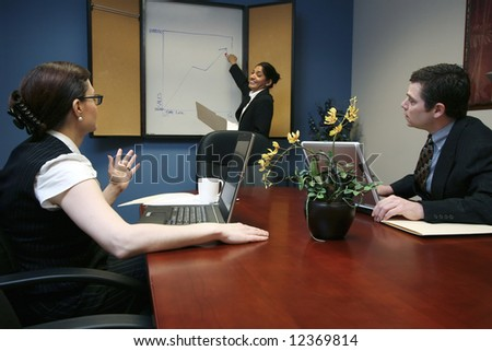 Indian businesswoman presenting to her colleagues during a meeting - stock photo