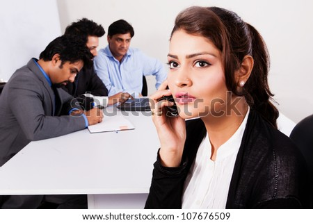 Indian businesswoman talking on the phone with her colleagues in the background