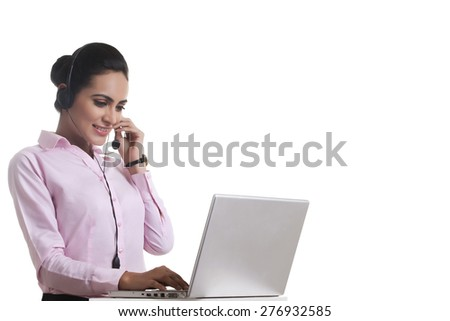 Indian businesswoman using headset and laptop isolated on white background - stock photo