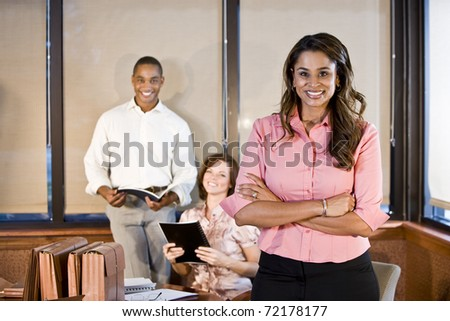 Indian businesswoman working in office with multiracial coworkers, focus on foreground - stock photo