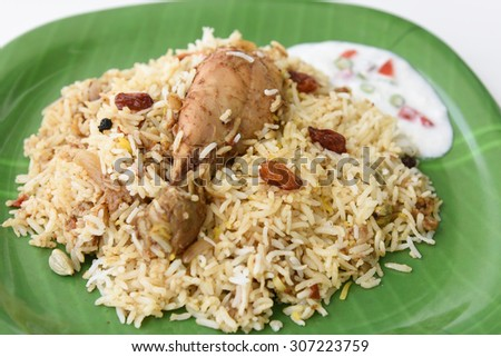 Indian Chicken Biryani/Biriyani or fried rice with chicken leg or drumstick and raita / curd/ yogurt in green plate on white background .closeup view of delicious chicken pulao with colorful garnish. - stock photo