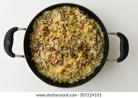 Indian Chicken Biryani/Biriyani or fried rice with chicken leg or drumstick in a pan on a white background .closeup view of delicious chicken pulao or pilaf with colorful garnish India Kerala. - stock photo