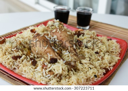 Indian Chicken Biryani/Biriyani or fried rice with chicken leg or drumstick served in a red plate with two glasses of red wine.closeup view of delicious chicken pulao or pilaf with colorful garnish. - stock photo