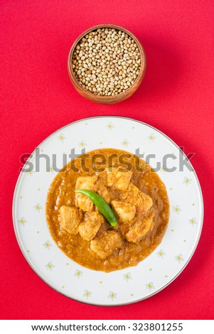 Indian chicken curry - Overhead view of spicy Indian chicken curry served on a plate pictured next to a bowl of coriander seeds, a key ingredient. Natural light used. - stock photo