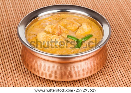 Indian chicken curry served in authentic copper bowl. Green chilli used as garnish. - stock photo
