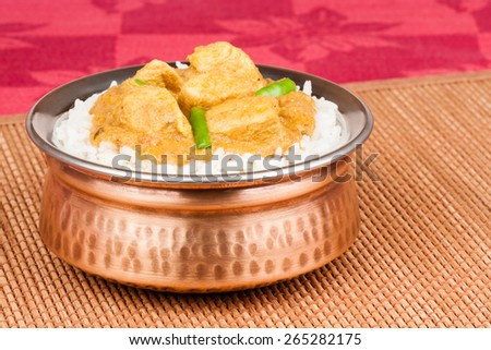 Indian chicken curry served on rice in authentic copper bowl. Green chilli used as garnish. - stock photo