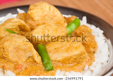 Indian chicken curry served on rice in authentic copper utensil. Green chilli used as garnish. Shallow Depth of field. - stock photo