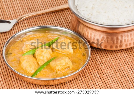 Indian chicken curry served with rice in authentic copper utensils. Green chilli used as garnish. - stock photo