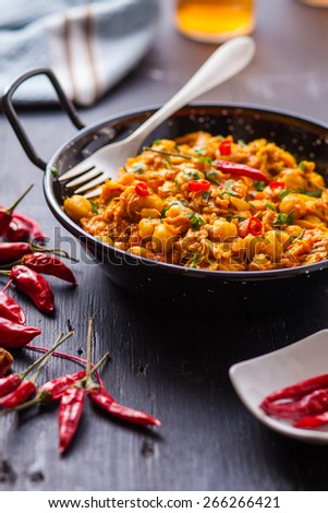 indian chicken curry with peas and chili pepper on pan - stock photo