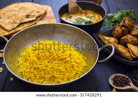 Indian chicken pilau rice in balti dish served with tikka masala curry, plain naan bread, vegetable samosas, and onion bhajis - stock photo