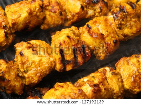 Indian chicken tikka kebabs cooking on griddle plate. - stock photo