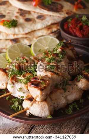 Indian chicken tikka kebabs on skewers close-up on a plate and naan. vertical