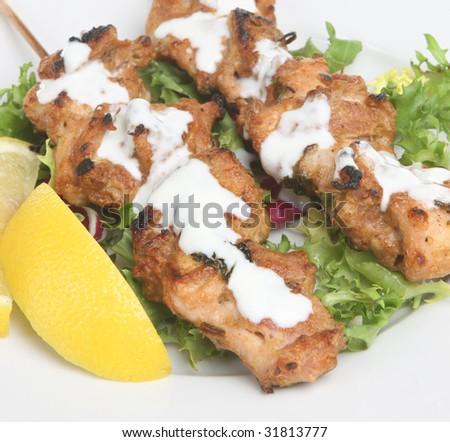 Indian chicken tikka kebabs with yoghurt & salad - stock photo