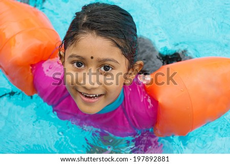 Indian child learning swimming in pool. Asian girl in swimmer class with float bands. - stock photo