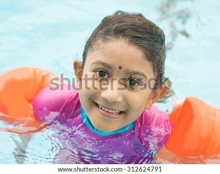 Indian child learning swimming in pool. Asian kid in swimmer class with float bands.