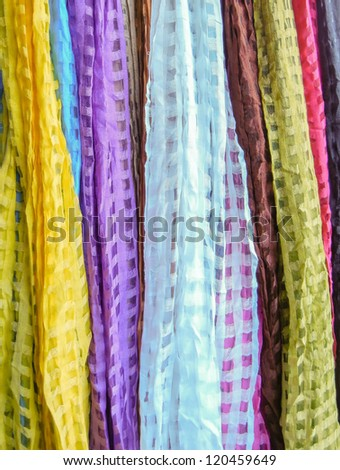 Indian colorful scarf in a row with vivid colors stripes on sell at roadside stall in Ahmedabad, India. Great for design element or backdrop. - stock photo