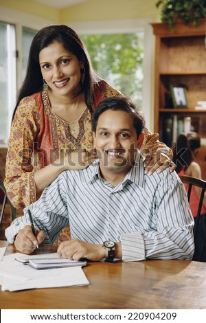 Indian couple paying bills at table - stock photo