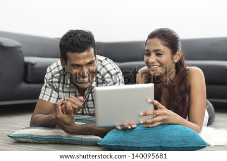 Indian couple relaxing with a digital tablet in their living room - stock photo
