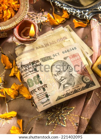 Indian currency notes with a traditional lamp. Currency is worshiped during Diwali festival as a God in India. - stock photo