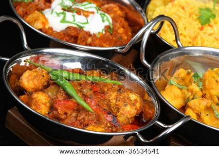 Indian curries in balti serving dishes - stock photo