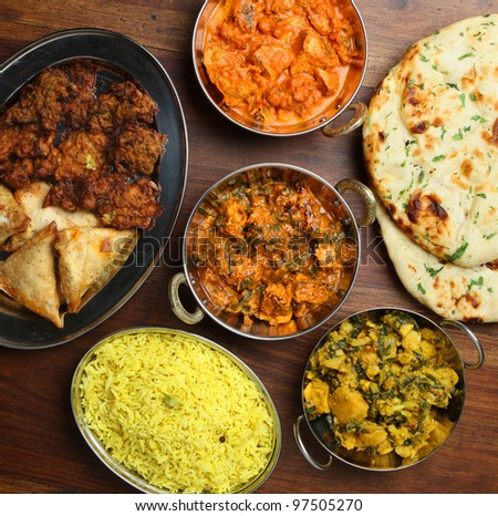 Indian curries with rice and accompaniments - stock photo